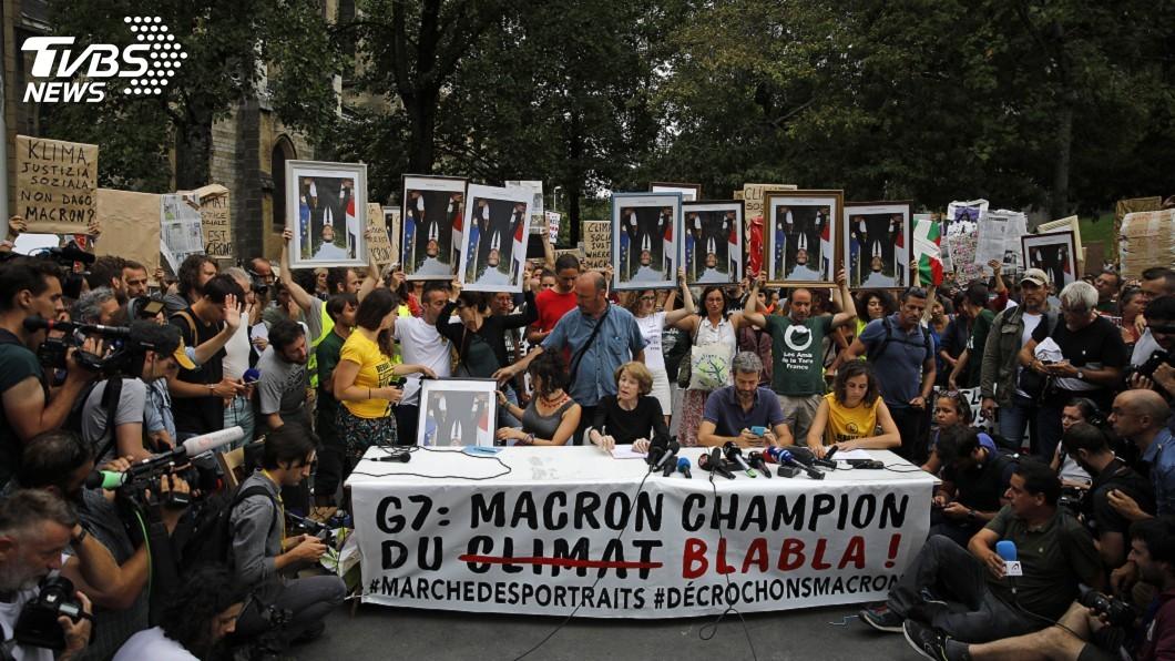 圖/達志影像美聯社 顛倒拿馬克洪肖像 G7抗議人士要法總統下台
