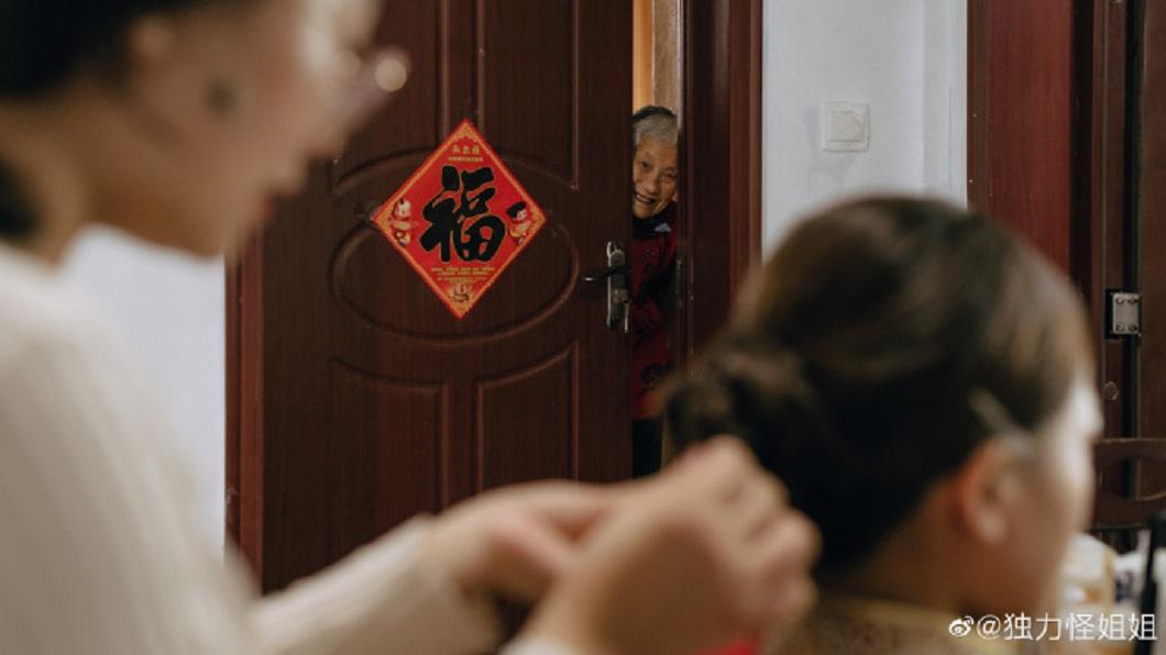 阿嬤躲在門後看著準備出嫁的孫女化妝,這一幕讓人眼淚決堤了。(圖/翻攝自微博) 嬤躲門後看孫女出嫁 這一幕被捕捉網淚崩:好想奶奶