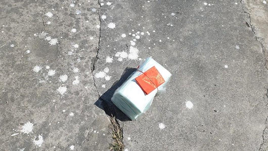 有網友曬出地面上厚厚一疊藍色不明物品,上頭還綁著一個紅包袋。(圖/翻攝自臉書社團「爆廢公社」) 路邊驚見一綑口罩綁紅包!「親家下重本」網笑:你先撿