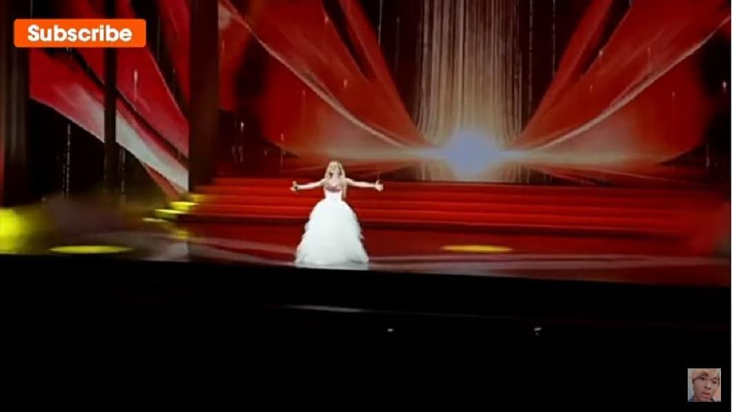 俄羅斯1名女歌手日前受邀參加在婦女節活動開唱。(圖/翻攝自YouTube) 女歌手踩空摔下舞台腳骨折 忍痛敬業完成表演