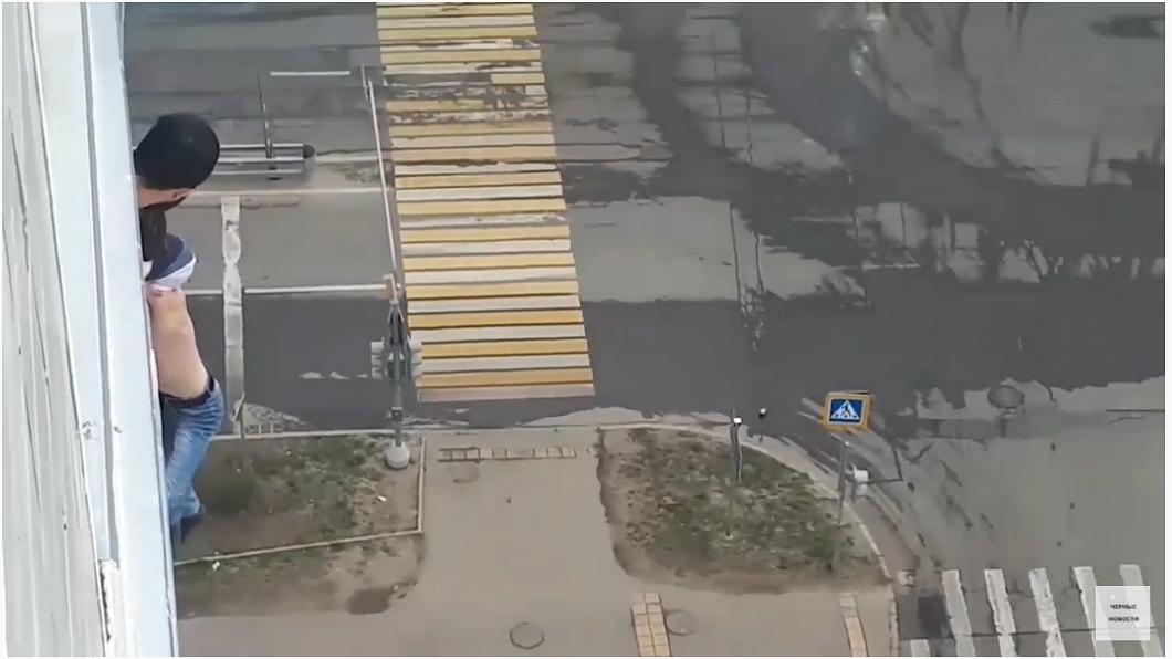 俄羅斯1名男子因喝茫而不慎失足滑倒,整個人掛在15層樓高的外牆。(圖/翻攝自YouTube) 男喝茫自拍滑倒…人垂掛15樓獲救 「離開家裡」慘受罰