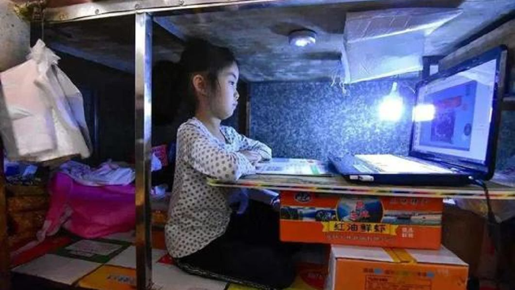 大陸1名7歲女童,疫情期間陪父母親去市場擺攤,自己則乖乖地在攤位底下念書。(圖/翻攝自新浪網) 7歲女每日陪父母擺攤窩攤下讀書 網封:亞洲版哈利波特