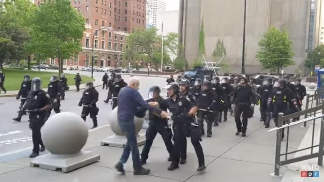 一段影片顯示,紐約州水牛城穿戴鎮暴裝備的警察將一名白髮男子推倒,似乎不予理會地持續往前推進。(圖/翻攝自WBFO YouTube) 非裔之死示威 紐約白髮男子遭警推倒頭破血流