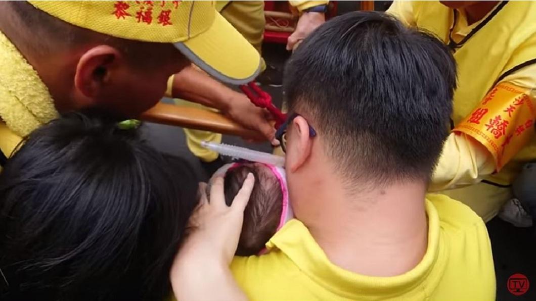 1對父母抱著插管的2歲女兒,祈求白沙屯媽祖可以為她賜福。(圖/「白沙屯媽祖網路電視台」授權提供) 父抱2歲插管女跪地求賜福 白沙屯媽為她急停惹哭信眾
