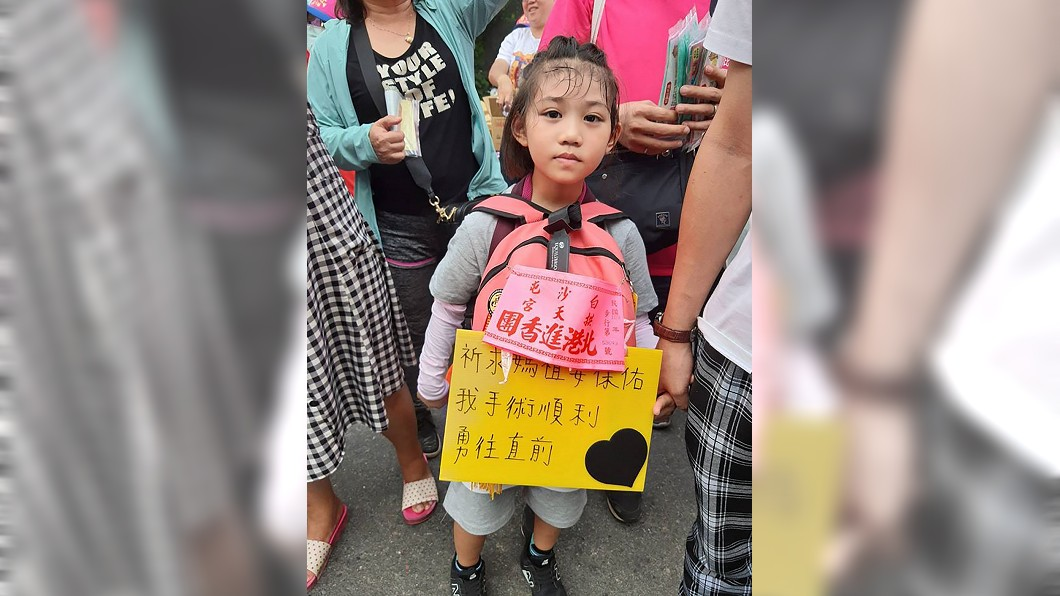 來自花蓮的羅小妹妹,身上揹著牌子寫著「祈求媽祖要保佑我手術順利,勇往直前」。(圖/中央社,民眾提供) 四度動刀 6歲女童揹牌祈願:希望白沙屯媽祖保佑我