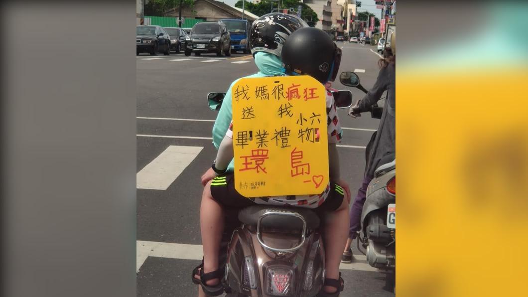 小學生背著黃色廣告板「我媽很瘋狂送我小六畢業禮物環島」。(圖/翻攝自臉書蔣敏全) 媽載小六生環島當畢業禮物 被讚最美教育風情畫