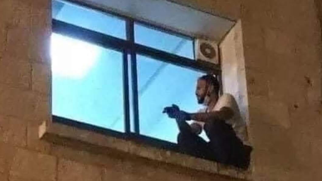 巴勒斯坦男攀2樓牆蹲病房窗口向染疫病危母親道別。(圖/翻攝自 Mohamad Safa twitter) 巴勒斯坦男攀牆蹲病房窗口 向染疫病危母親訣別