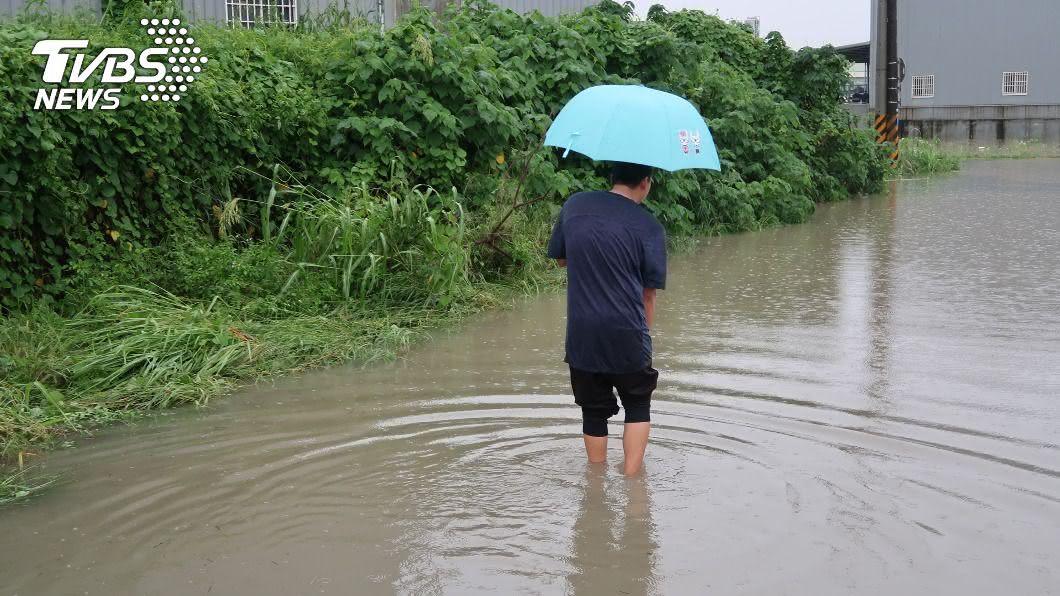 高雄市因豪雨多處地區淹水,令民眾涉水難行。(圖/中央社) 高雄豪雨五甲尾排水溝近滿水位 河岸道路淹到小腿