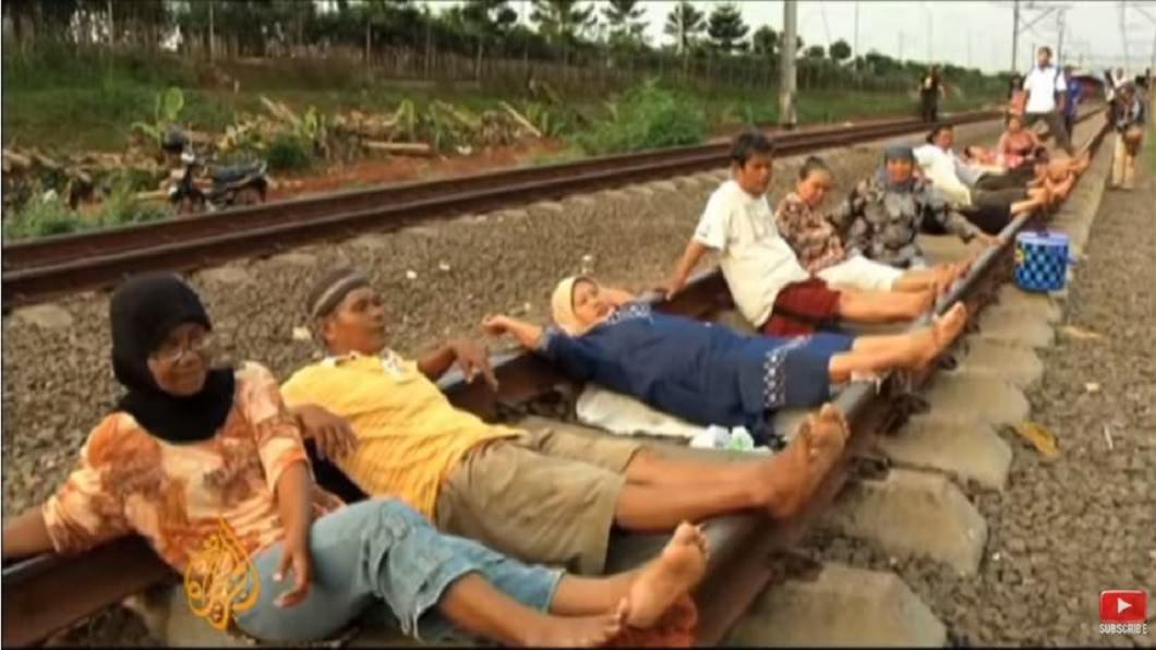 印尼一處村落流行「臥軌電療法」,認為即將通過的火車所帶來的電流導入人體可以治百病。(圖/翻攝自YouTube) 堅信「躺臥鐵軌」治百病 印尼村民躺整排瘋電療