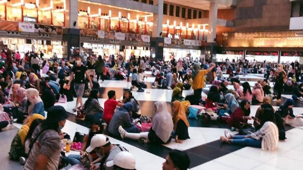 有網友拍下北車大廳許多席地而坐的民眾沒戴口罩。(圖/翻攝自臉書社團「爆怨公社」) 席地而坐再惹議!網見「群聚沒戴口罩」轟爆:防疫破口