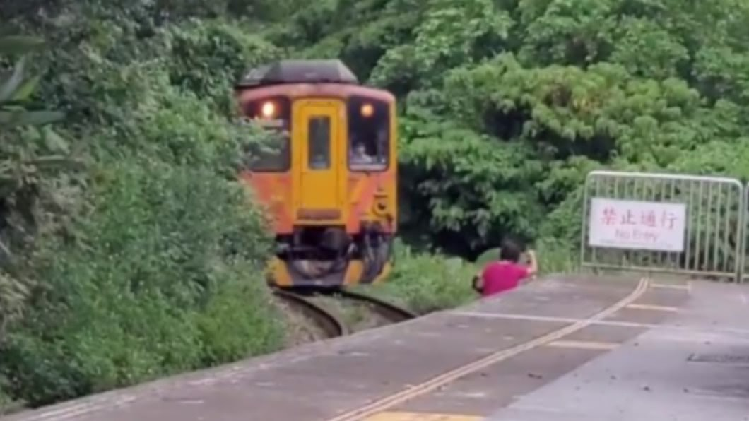 婦人擅闖鐵軌險遭撞。(圖/翻攝自臉書) 差點輾過!婦人「闖鐵軌自拍」 火車狂按喇叭急煞進站