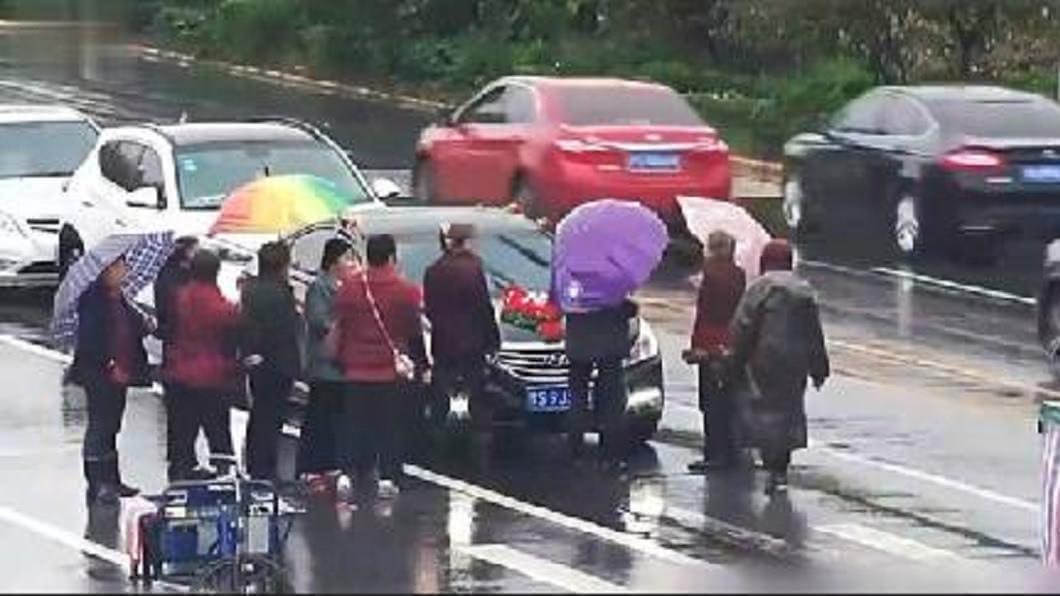 大陸河南日前發生一群老人組團攔禮車討紅包的事件。(圖/翻攝自微博) 30老人組團攔禮車討紅包 趴車頭直嗆:不給就不准過