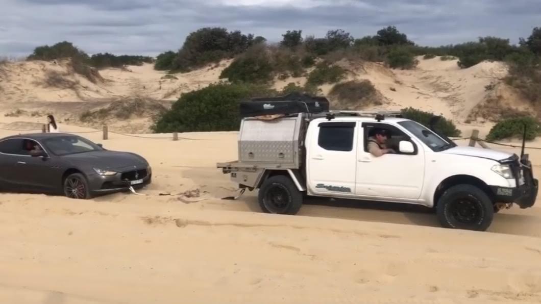 一輛跑車陷入沙灘動彈不得,請求吉普車支援。(圖/翻攝自Ian Boicos臉書) 500萬跑車困沙灘!好心救援害「車頭爆開」保險桿噴出