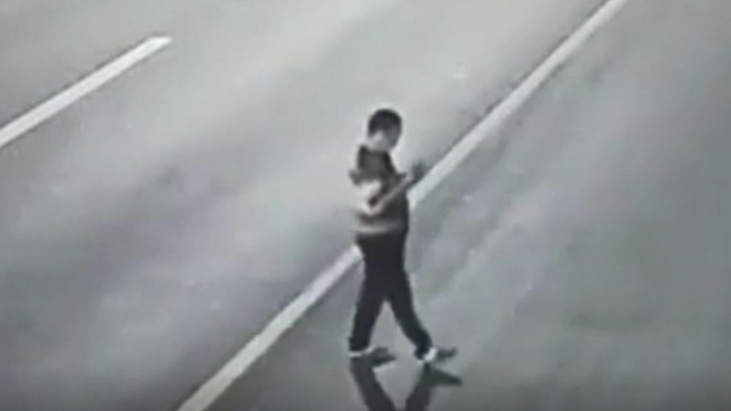 男子停在路中間滑手機。(圖/翻攝自《南國早報》) 男顧滑手機佇立路中央 遭轎車撞飛空轉1圈砸地