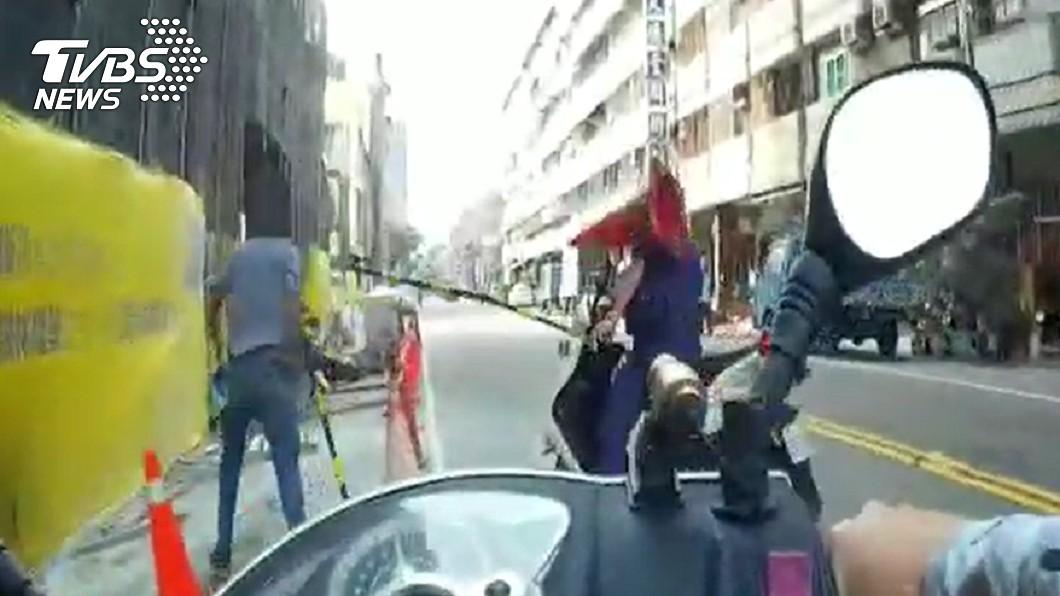 男子拿「三角錐」攻擊前來追捕的員警。(圖/TVBS) 揹3條通緝遇警心虛!高雄男街頭狂奔 遭包抄壓制慘了