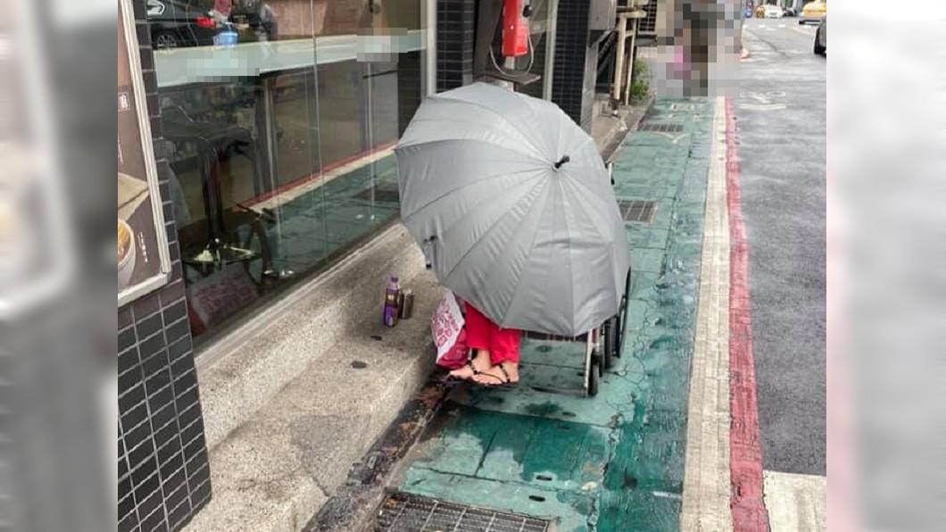 阿嬤路旁獨坐輪椅上。(圖/翻攝自臉書社團「爆料公社公開版」) 嬤被推路旁「給冷風吹」瑟縮撐傘抖 外籍看護跑嘸影