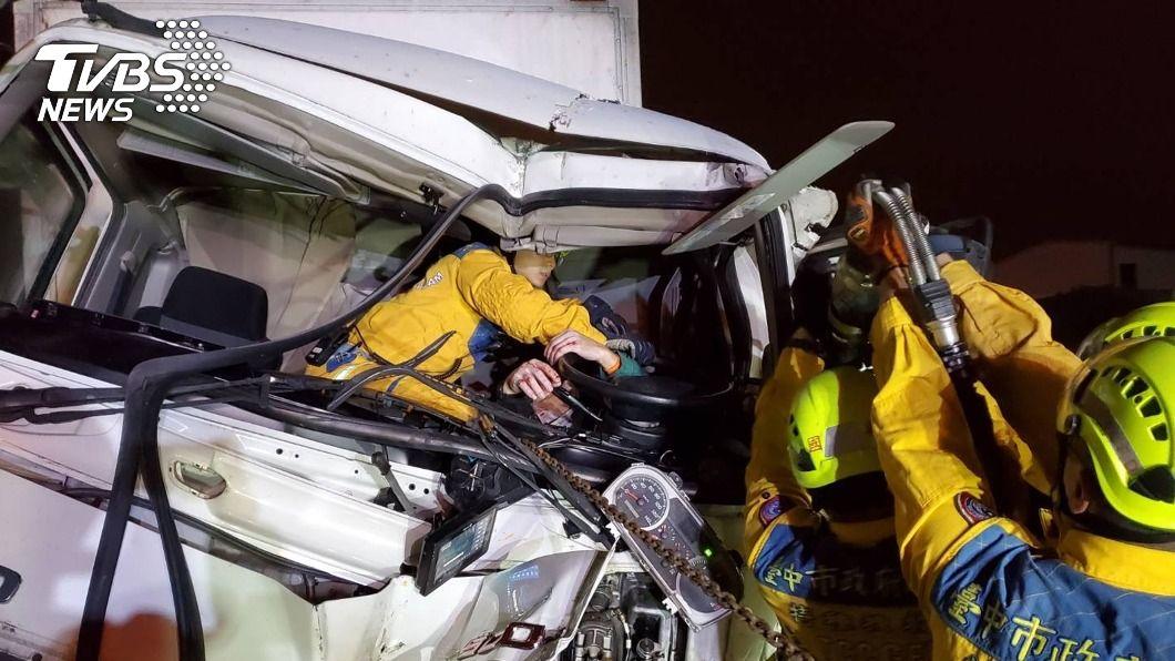 消防救護人員將受困貨車駕駛救出。(圖/中央社) 國道1號台中路段貨車追撞 駕駛受困車內救出