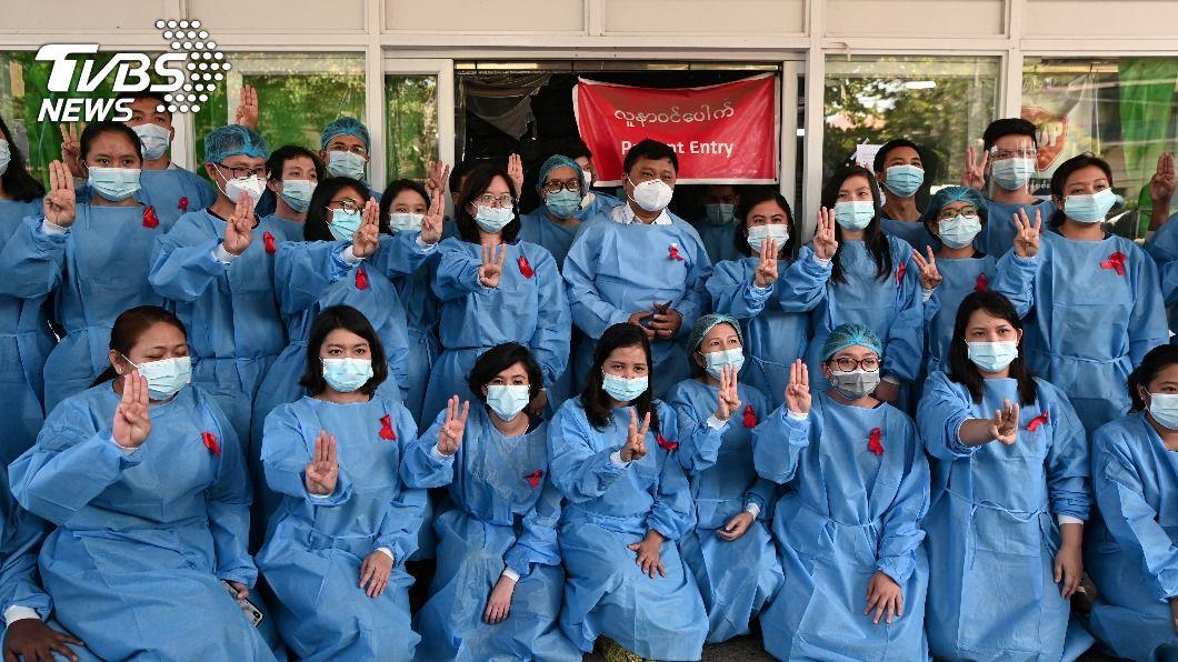 緬甸仰光的醫護人員高舉三指聲援翁山蘇姬。(圖/達志影像路透社) 《飢餓遊戲》舉三指抗爭 泰國香港緬甸相繼仿效