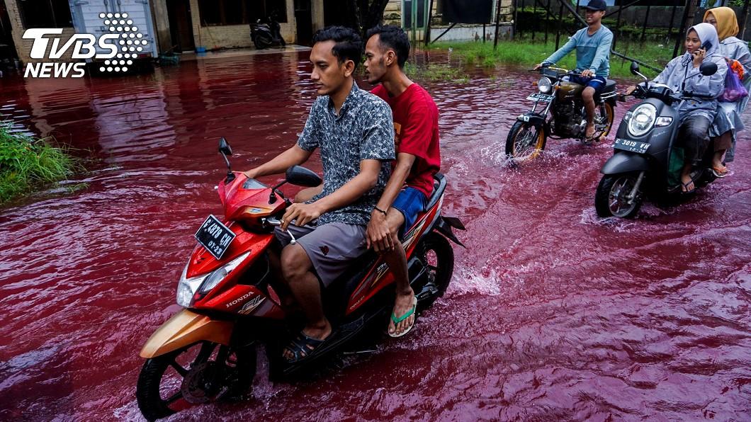 北加浪岸民眾在紅色雨水中騎機車前進。(圖/達志影像路透社) 天降紅雨?洪患狂襲印尼村莊 「血流成河」畫面曝