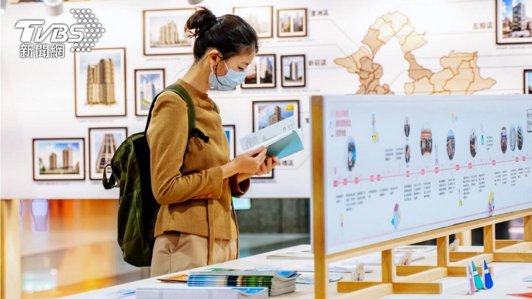 民眾在展覽中閱讀書冊。(圖/新北市政府都更處提供) 新北市府攜手金點設計團隊 推出「都更工具書」貼近民心