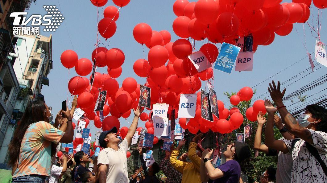 緬甸民眾握著紅色氣球呼籲國際出面干預軍政府血腥鎮壓。(圖/達志影像美聯社) 緬甸瓦城示威8人喪命 民眾不懼今晨再集會抗議