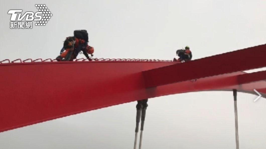 一名年約29歲的男子因不明原因獨自爬上淡水關渡橋。(圖/TVBS) 險象環生!男上爬12公尺關渡橋 警消封路急救援