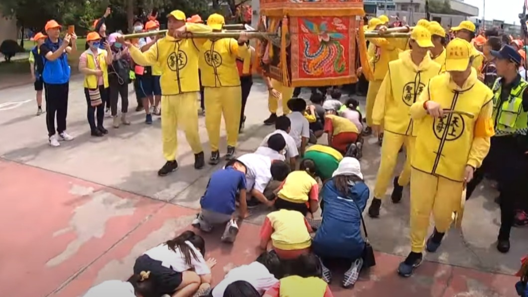 白沙屯媽祖造訪國小 學童搶「跪地鑽轎底」
