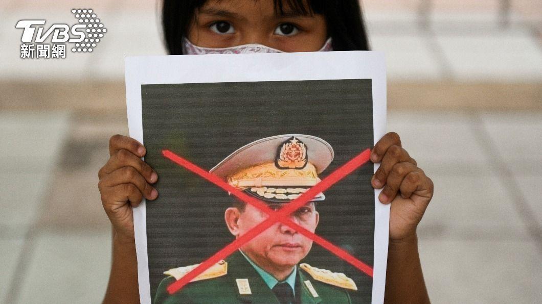 一名泰國女孩舉著反抗緬甸軍政府領導人的宣傳文宣。(圖/達志影像路透社) 緬甸軍政府領導人明抵雅加達 印尼民團抗議