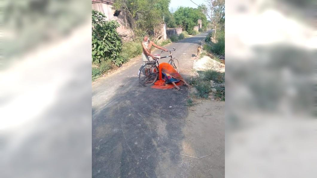 印度一名老翁的妻子染疫身亡被村民拒絕火化遺體。(圖/翻攝自推特) 村民拒絕火化憂傳染 印度7旬翁扛亡妻遺體蹲路邊哭