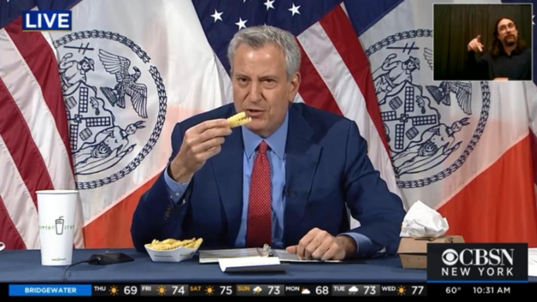 紐約市長白思豪13日記者會宣布與Shake Shack合作推疫苗,在會中大玩「吃播」吸民眾接種。(圖/截取自CBSN新聞畫面) 紐約市長攜手知名速食品牌推疫苗 記者會大玩「吃播」