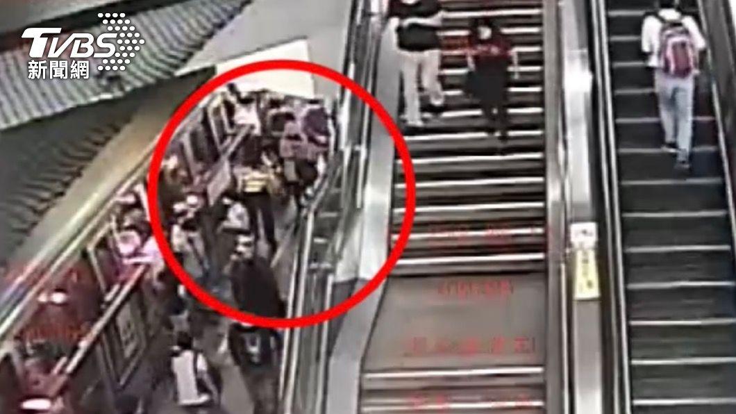 男子輕拍粉色上衣女子的左側身體。(圖/TVBS) 妙齡女控性騷擾 捷運內噴防狼劑遭告傷害 還波及站務員