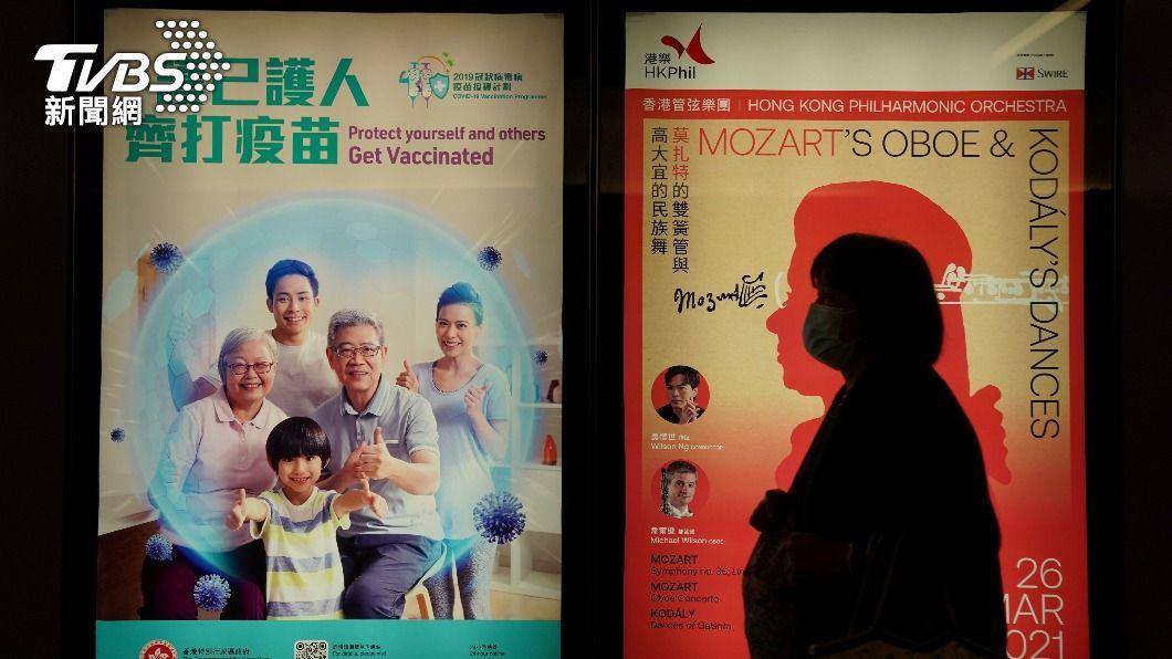 一名香港民眾經過鼓勵民眾施打疫苗的宣導海報。(圖/達志影像路透社) 香港173萬人接種疫苗 開放12至15歲少年施打
