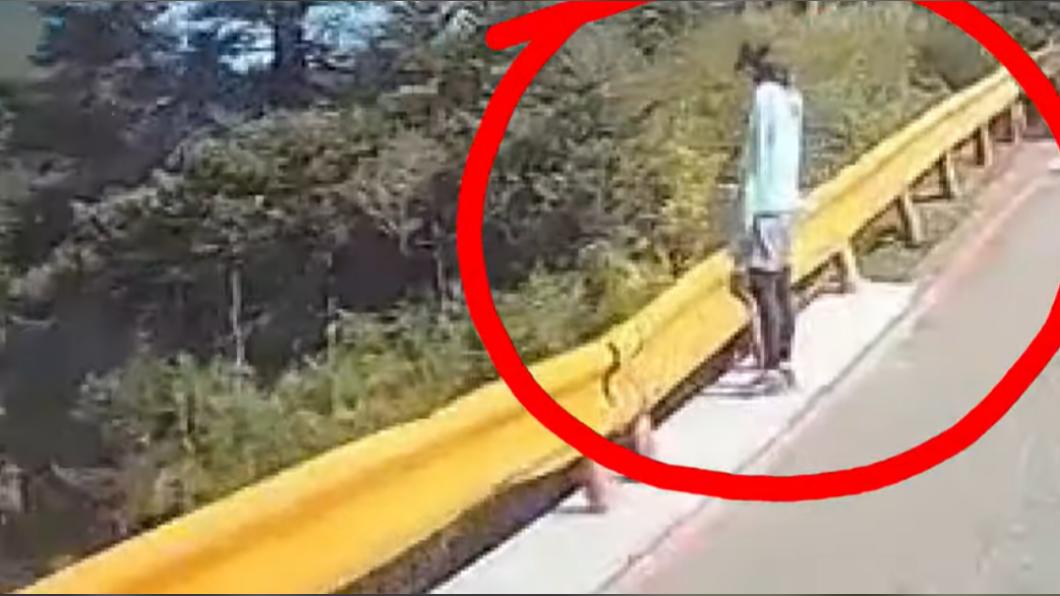 一名婦人欲靠坐公路護欄,不小心手滑翻落護欄。(圖/翻攝自當事駕駛YouTube) 合歡山傳溫情!婦倒栽翻護欄險摔懸崖 他違停狂奔救人