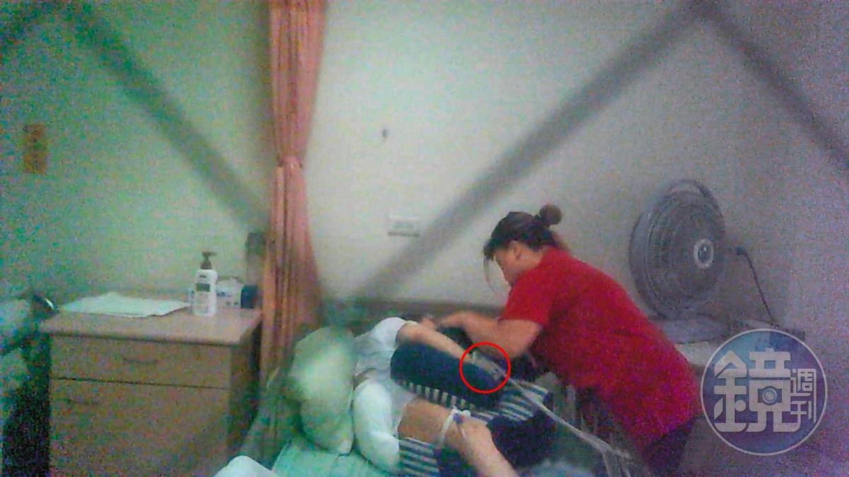 長生老人養護中心內一名台籍照服員正用束帶把老人的雙手綁在床的二側。