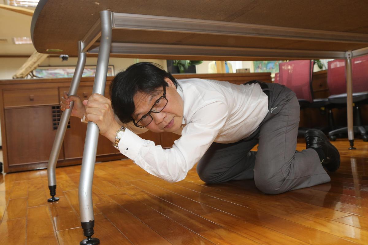 內政部長葉俊榮,配合台灣抗災資訊網的宣導,親身演練避難姿勢。(台灣抗災資訊網提供)
