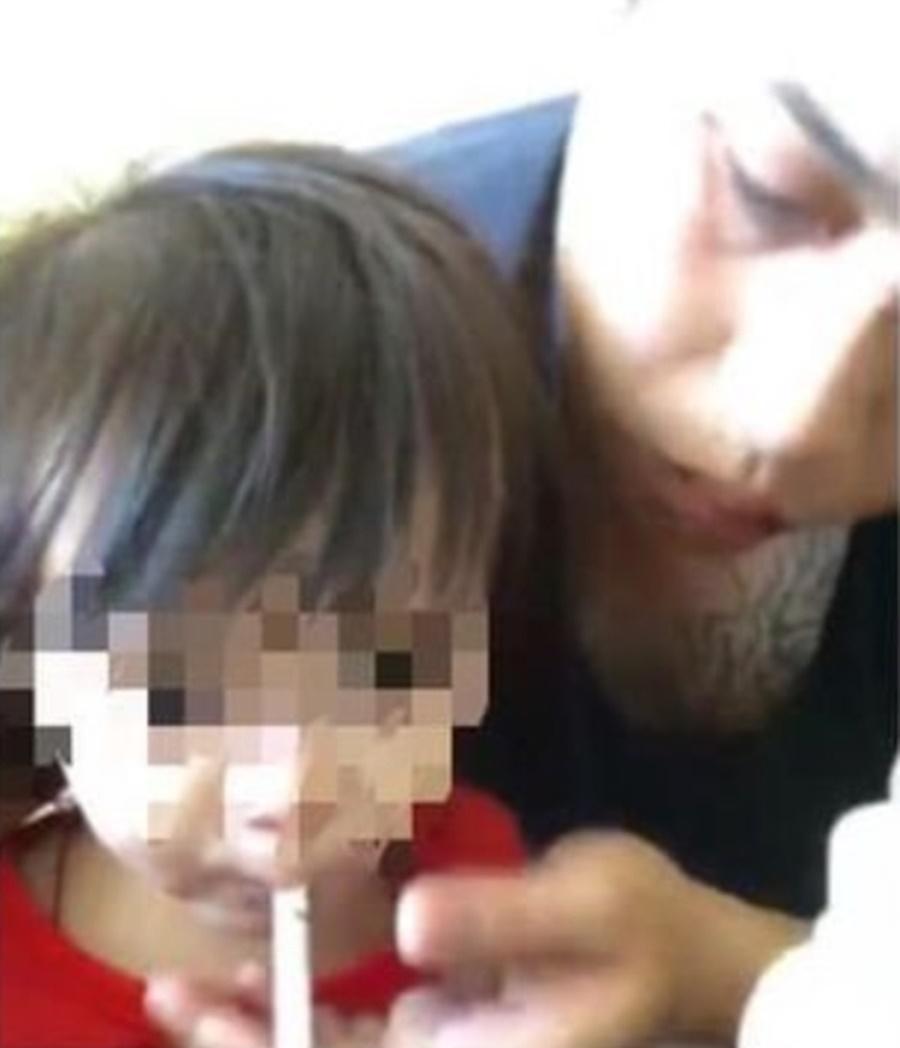 陳姓男子位女童抽菸。(翻攝畫面)