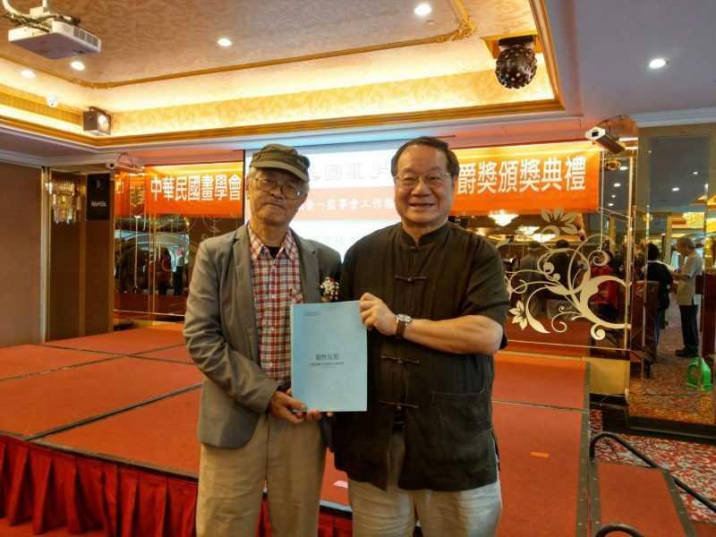 曾長生教授贈送著作給理事長唐健風。(畫學會提供)